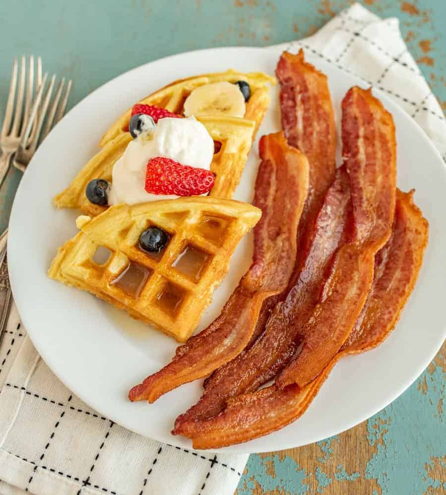 Tips and tricks you need to know so that you can cook crispy bacon in a cast iron skillet any day of the week.Bacon and waffles on a plate.