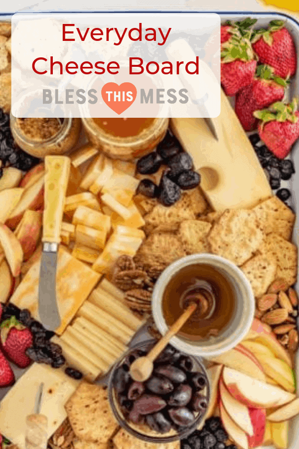 Title Image for Everyday Cheese Board with a variety of cheeses, crackers, olives, fruit, nuts, and spreads arranged on a serving tray