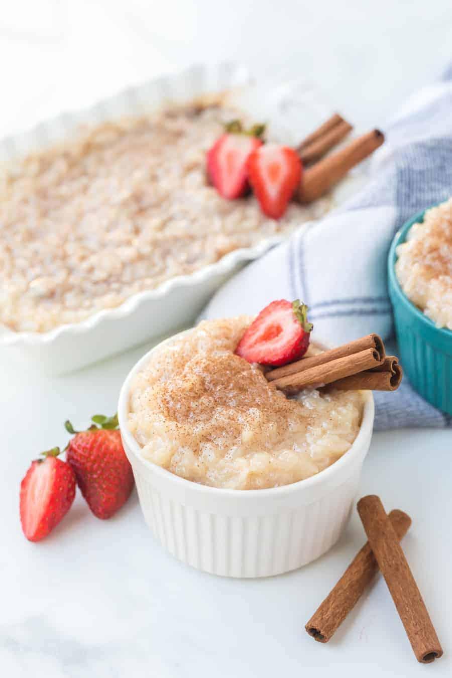 Rice pudding with strawberries and cinnamon sticks in ramekins