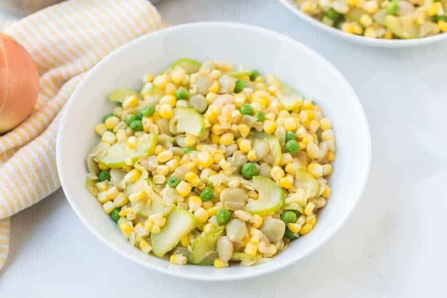 Zucchini and fresh corn succotash is a light and bright side dish that comes together easily and quickly with onion, zucchini, corn, and lima beans (plus a little hot sauce, if you like it)! #succotash #zucchinisuccotash #succotashrecipe #simplesuccotash #southerncooking #southernsides