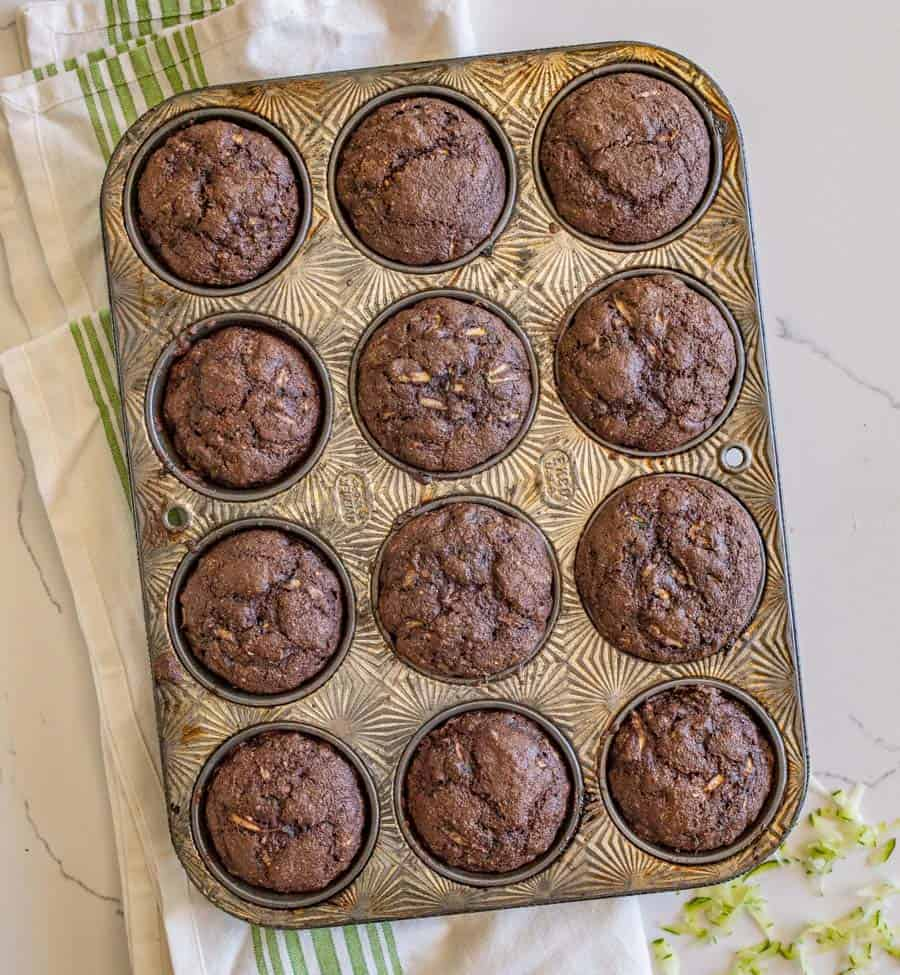 Healthy chocolate zucchini muffins are so yummy and make for a perfect snack or lunchtime dessert, made with whole wheat flour, maple syrup, applesauce, grated zucchini, and mini chocolate chips! #chocolatemuffins #zucchinimuffins #muffins #healthymuffins #muffinrecipe #chocolatezucchinimuffins