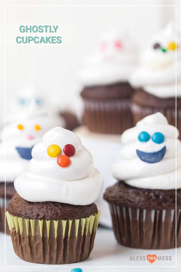 Chocolate cupcakes with white frosting and colorful candy faces