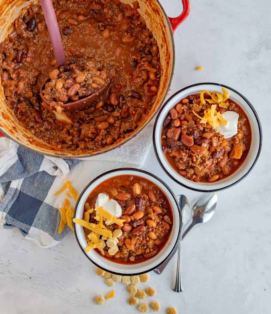chili in two bowls being served from large dutch oven