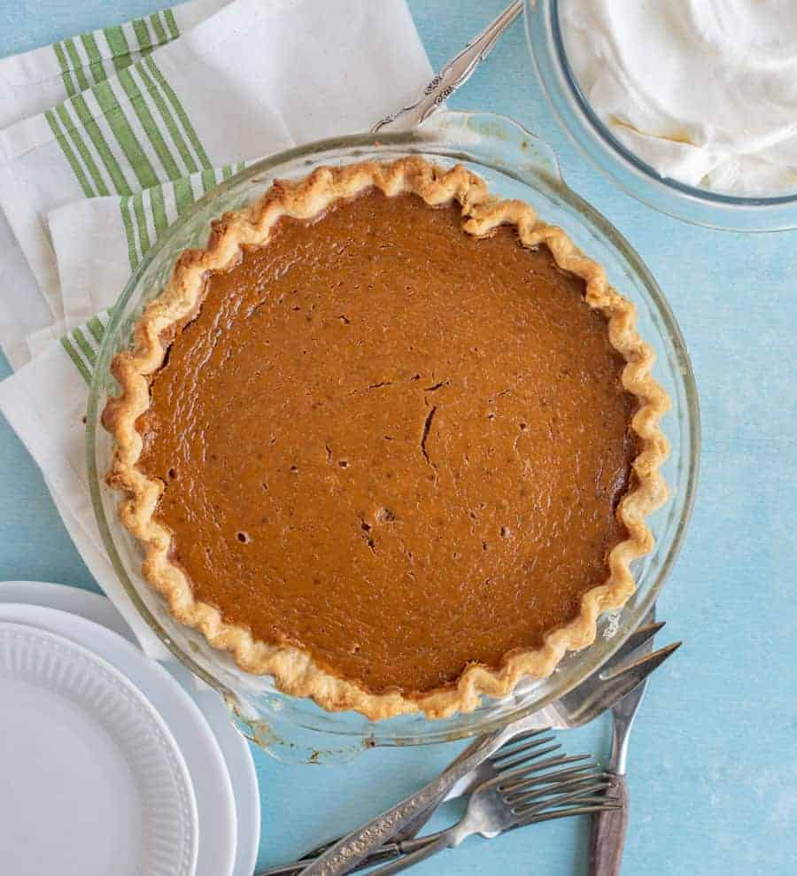 Overhead shot of a baked pumpkin pie in a glass pie dish on a blue counter. A glass bowl with whipping cream is in the top right corner. In the bottom right are some white dessert plates and at the bottom of the pie are some silver forks.