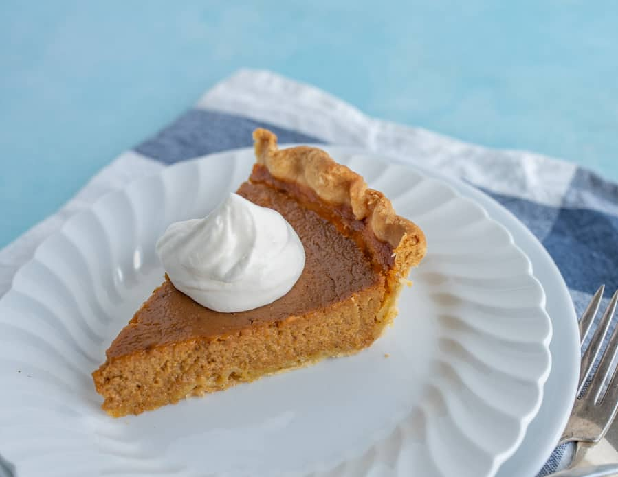 A piece of pumpkin pie from the side on a white dessert plate with a dollop of whipping cream on top.