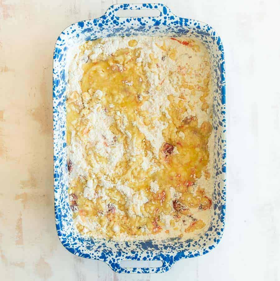 Overhead shot of a blue and white speckled rectangular pan filled with the ingredients to make a cherry dump cake.