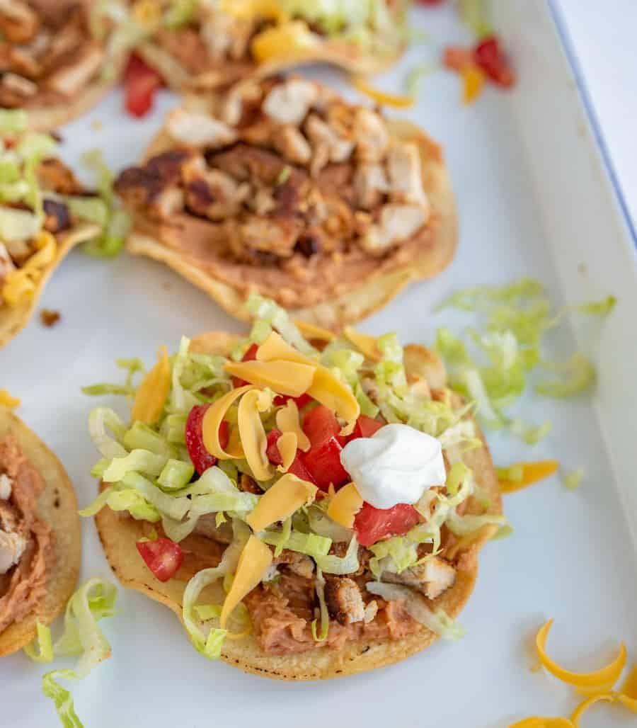The best chicken tostadas take only 30 minutes to make, including simple baked tostada shells, and the whole family will love them.They come together quickly and they're bursting with flavor, which is kind of the best thing ever when it comes to weeknight meals. #tostadas #chickentostadas #tacos #texmex #mexicanfood #tostadarecipe