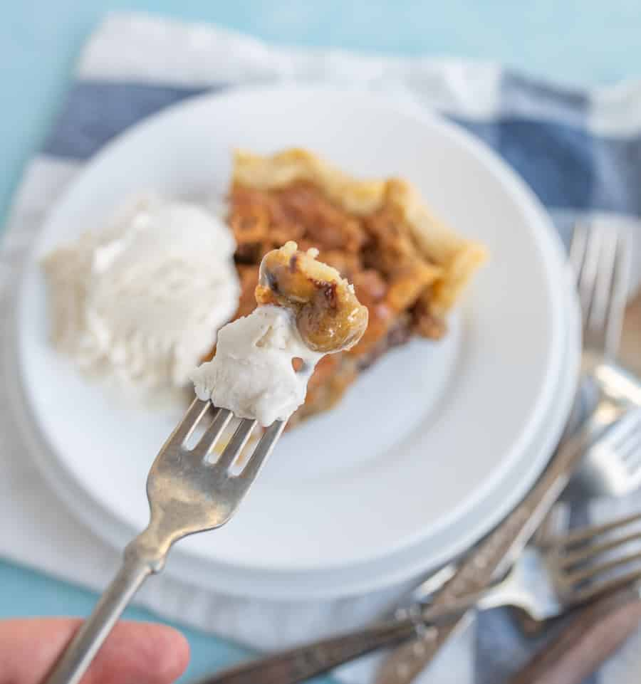 In the foreground, there is a piece of pie and a bite of vanilla ice cream on a fork being held with a finger showing. In the background is a piece of pie and a scoop of vanilla ice cream on a plate on top of a blue and white checkered towel and forks around the bottom right side.