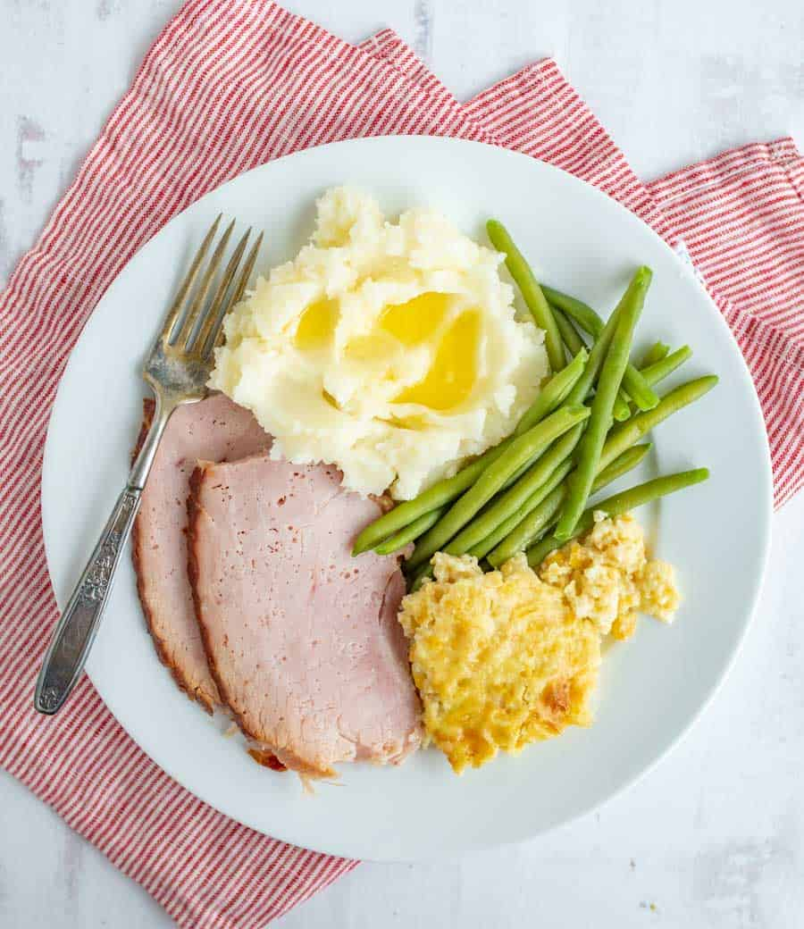 An above shot that shows an entire white dinner plate, complete with corn pudding in the bottom right, green beans above that, mashed potatoes with butter melting on them in the upper middle, ham in the bottom left, and a fork next to the ham and potatoes. Underneath the white plate is a skinny striped red and white towel.