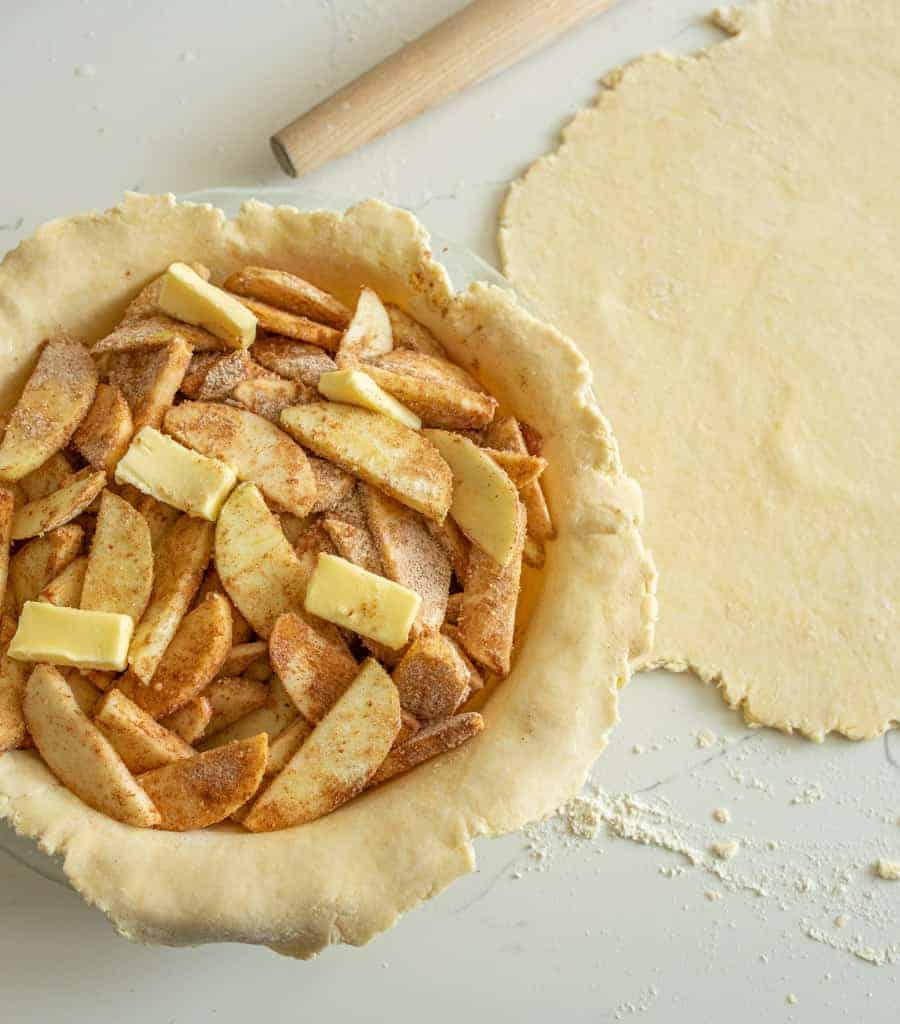 pie crust dough in pan with apples in, ready for a top and baking