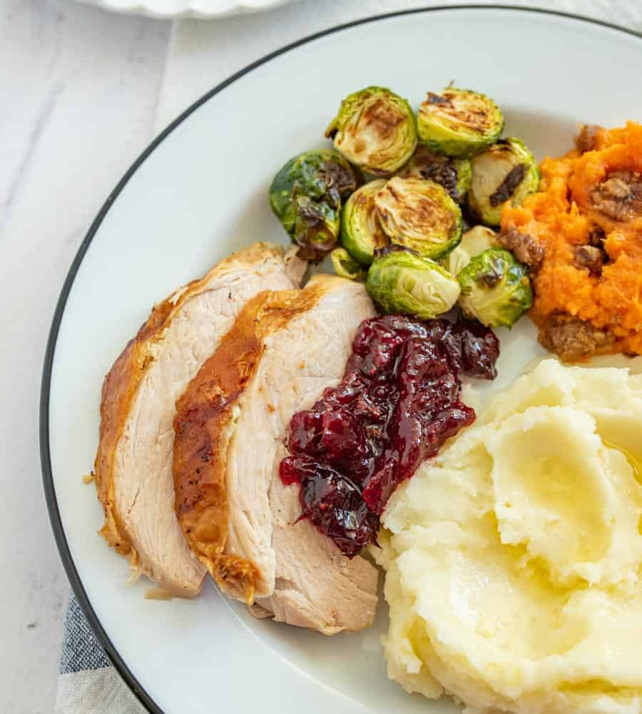 Two slices of cooked turkey breast with some cranberry sauce on it next to mashed potatoes, yams, and artichokes on a white dinner plate outlined with green.