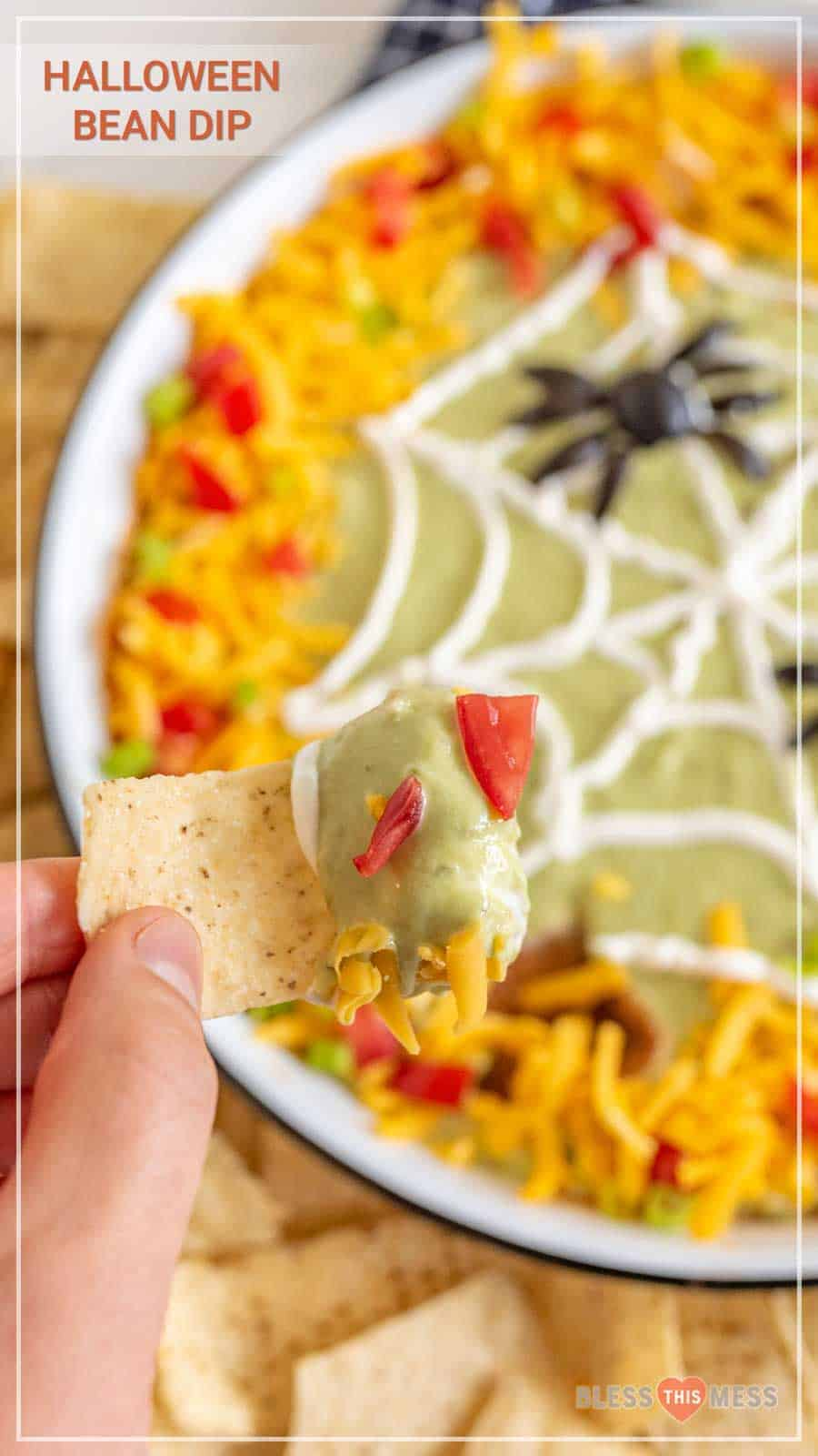 This easy Halloween bean dip is a no-bake recipe full of delicious ingredients that is SO easy to make, and its simple sour cream spider web makes it perfect to bring along to all your Halloween festivities! Wondering what to bring to this year's Halloween party? This bean dip is such a breeze to whip up (no cooking involved) and it looks intricate even though it's so easy, fast, and tasty! #beandip #layeredbeandip #refriedbeans #halloweenrecipes #halloweenbeandip #chipsanddip
