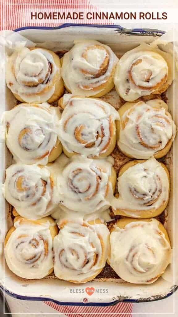 A baking dish with a dozen cinnamon rolls with frosting