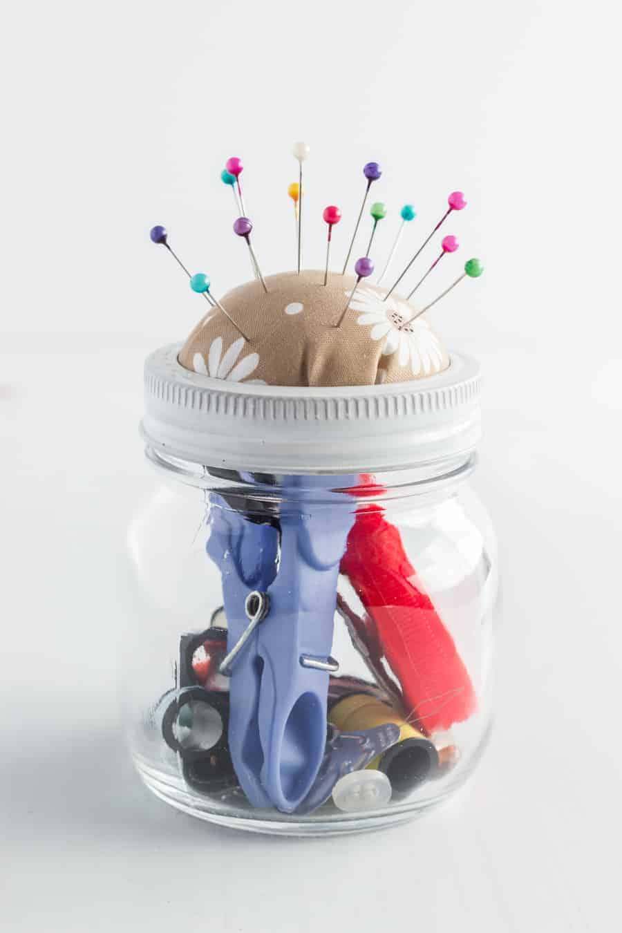 A jar full of sewing tools and the lid made into a pin cushion.