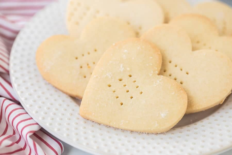 A close up of shortbread heart shaped cookies on a decorative white plate, on top of a red and white striped dish towel.