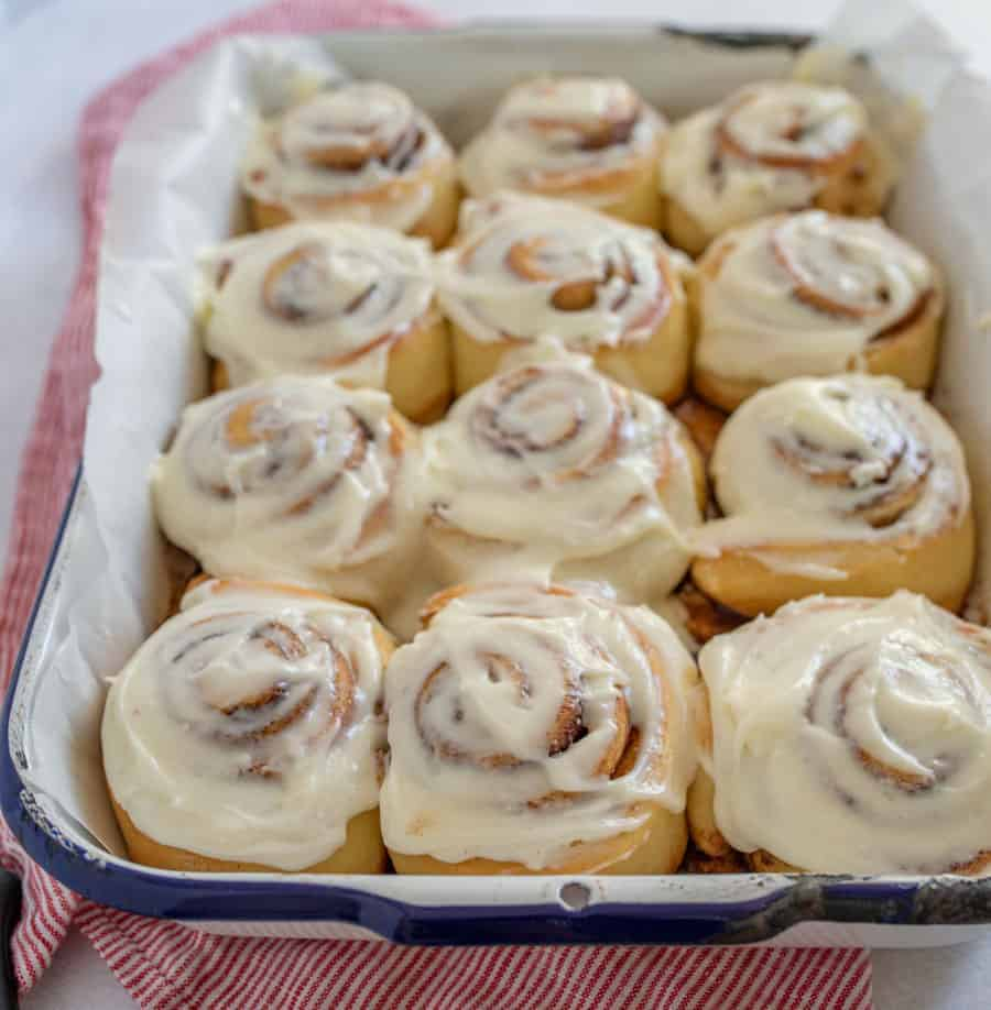 A closeup of the finished cinnamon rolls covered in frosting.