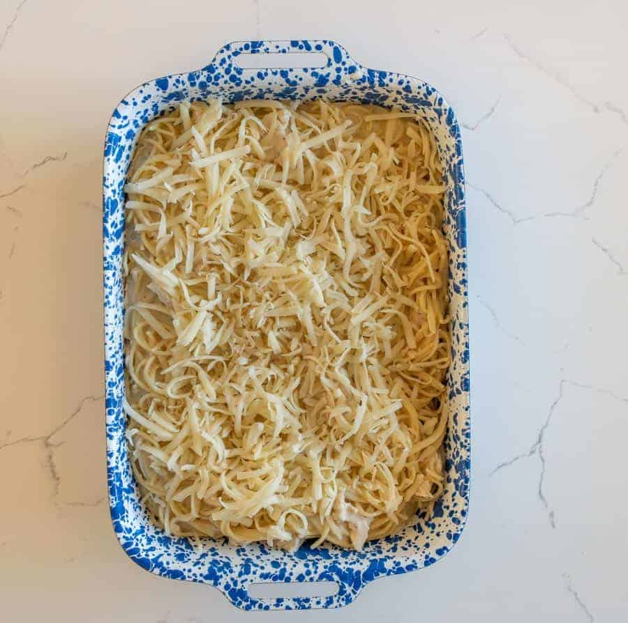 An overhead shot of the pasta all mixed, covered in grated cheese inside a ceramic rectangular pan that is white with bright blue speckles, on top of a white granite counter top.
