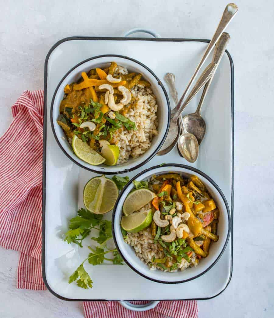 two bowls of easy vegetable curry on white serving tray with spoons