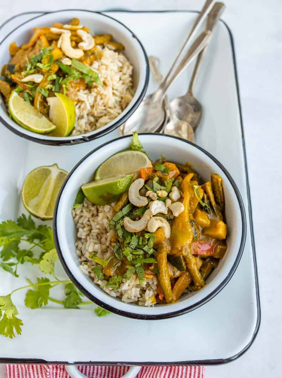 two bowls of easy vegetable curry on white serving dish with spoons