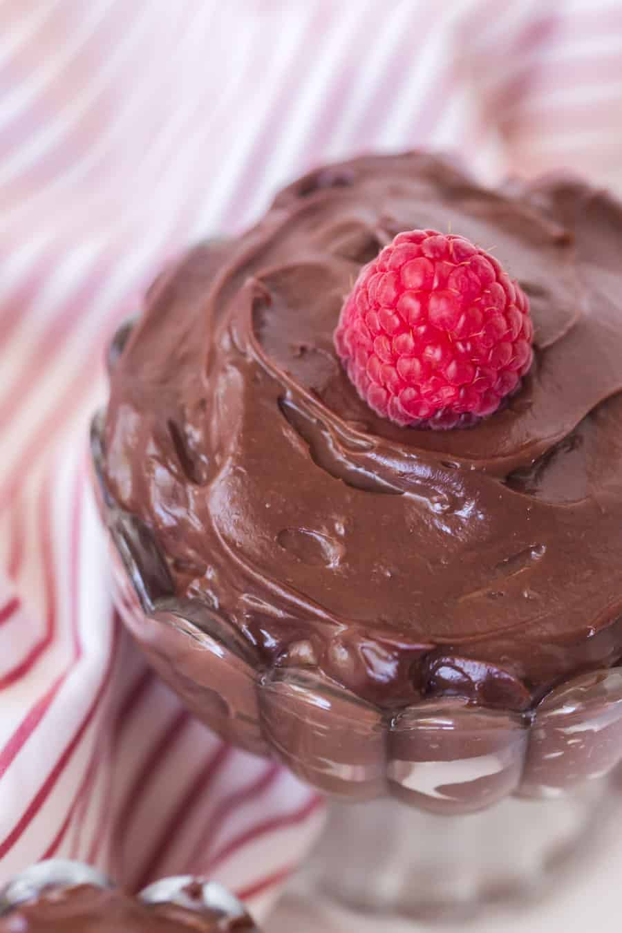 chocolate pudding in a pretty dish with raspberry on top