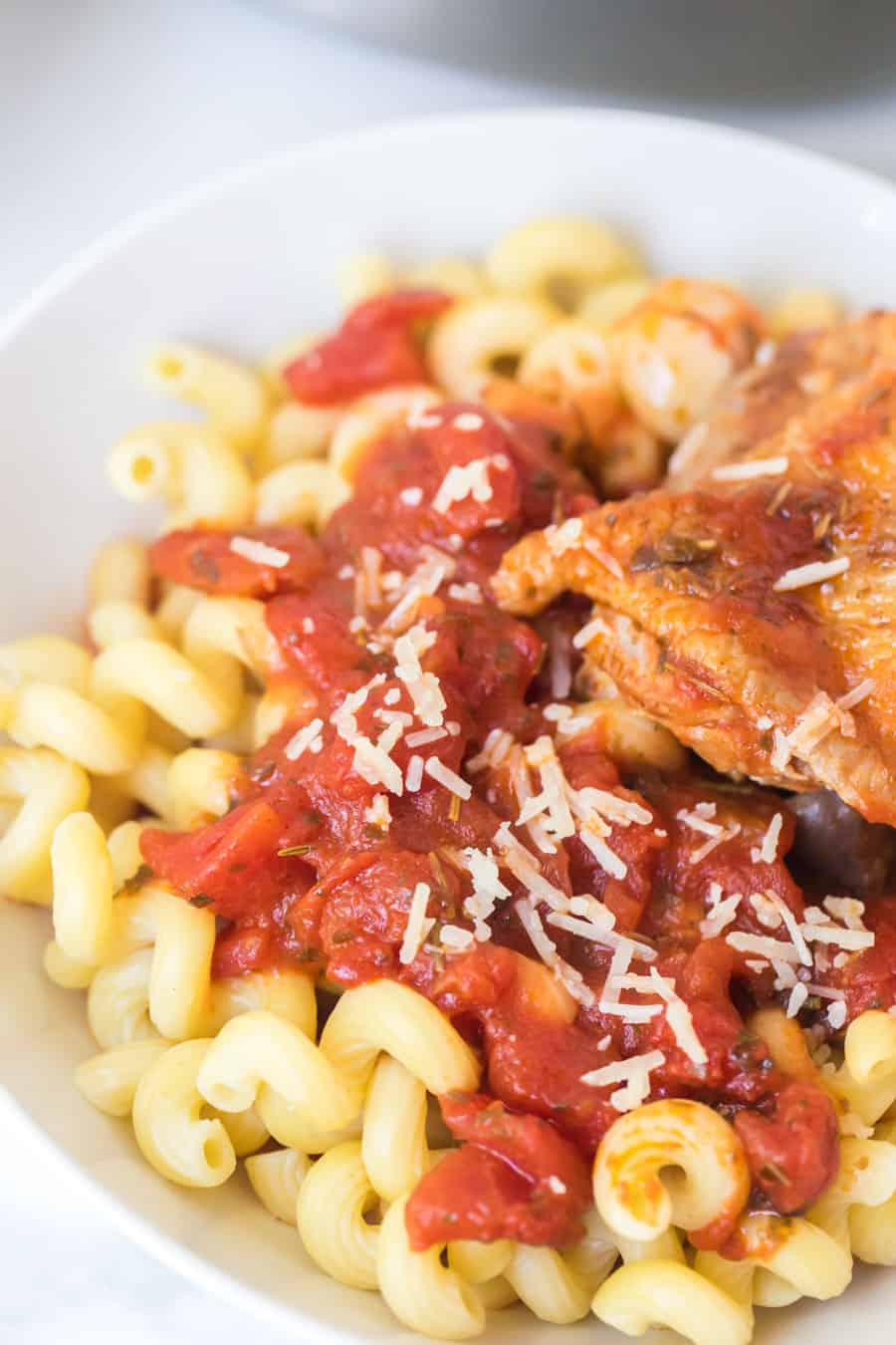 tomato and garlic pasta with chicken thigh in white bowl