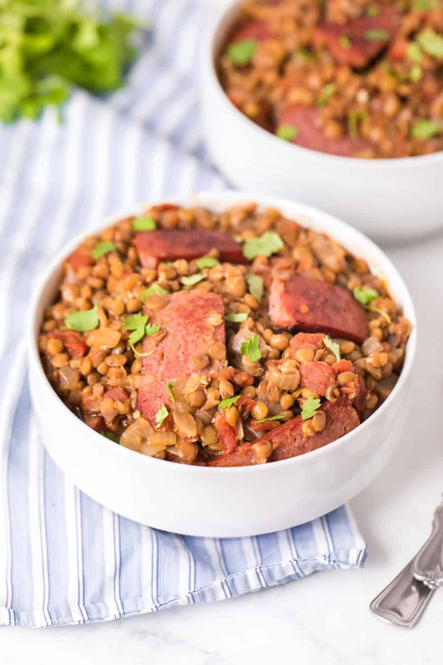 two white bowls of Spicy Lentils with Sausage