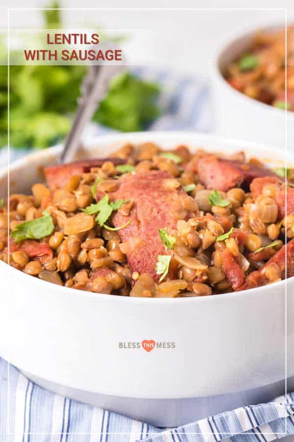 spicy lentils and sausage in white bowl with fork