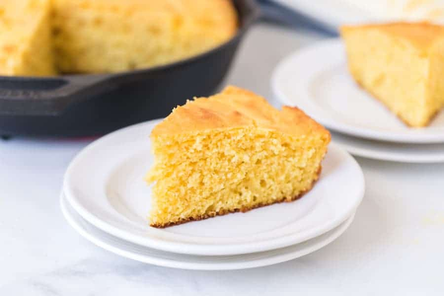 one slice of cut cornbread on a white plate ready to eat