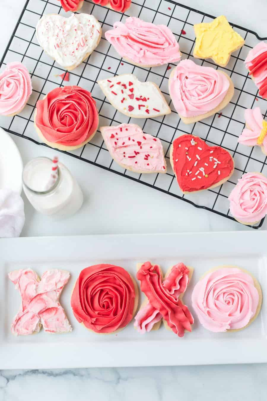valentine's day iced sugar cookies in heart shape lip shape and circle cutout cookies on cooling rack