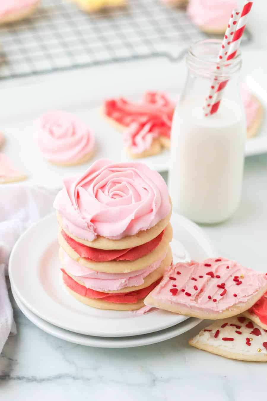 stack of pink and red iced sugar cookie cutouts on white plate with small glass jug of milk with red and white paper straws