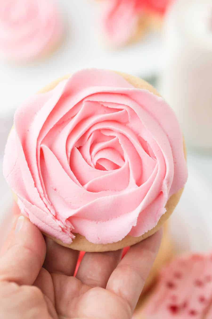 woman holding iced sugar cookie cutout with pink rose icing