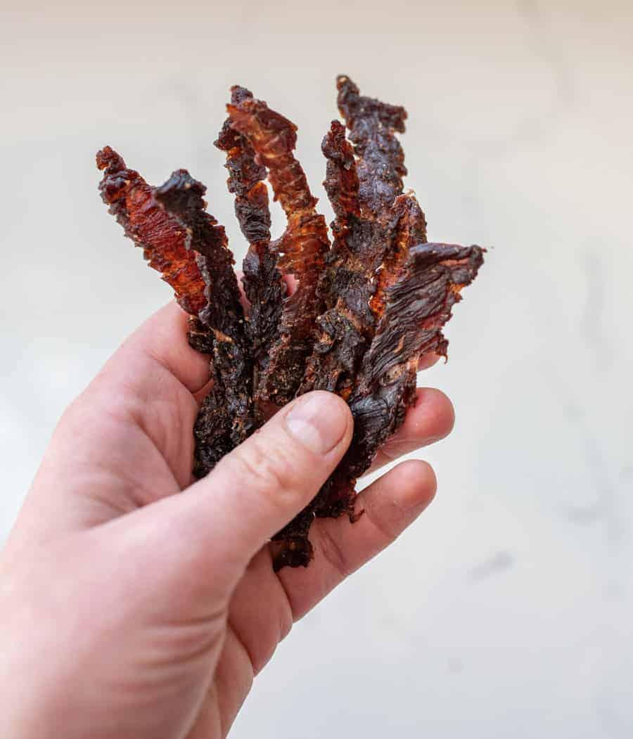 woman holding beef jerky strips closeup