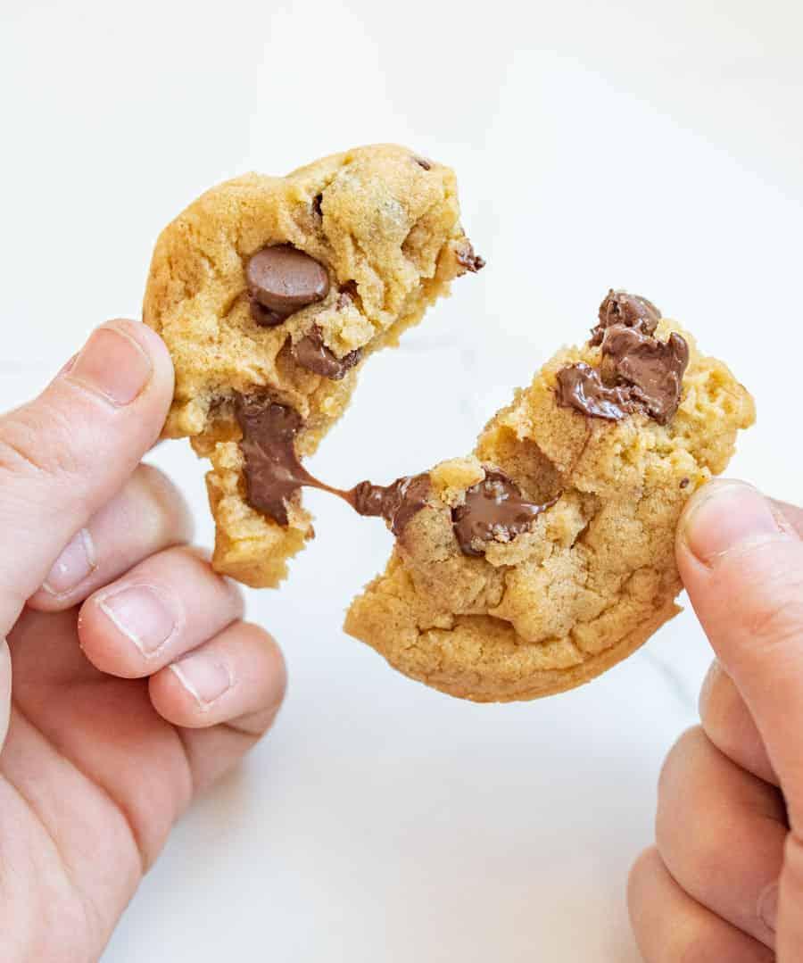 woman breaking apart chocolate chip cookie