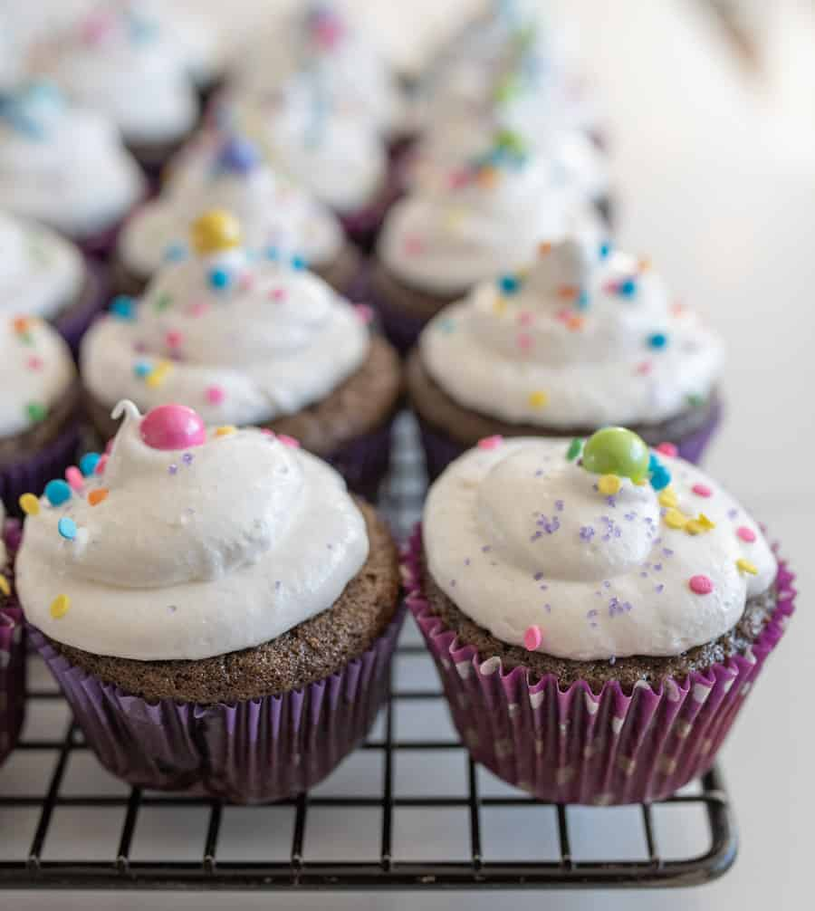 chocolate cupcakes with fluffy vanilla frosting and sprinkles on cooling rack