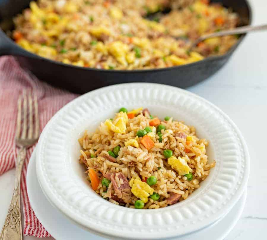 easy fried rice in a round white bowl next to skillet of fried rice