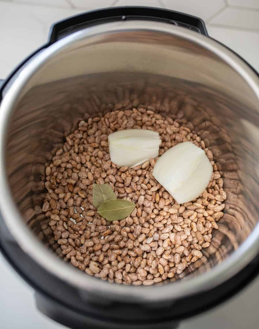 uncooked pinto beans with two pats of butter and two bay leaves