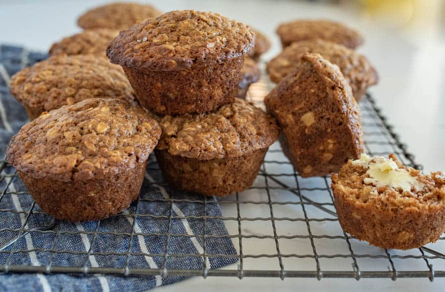 brown sugar oatmeal muffins with butter stacked on cooling rack