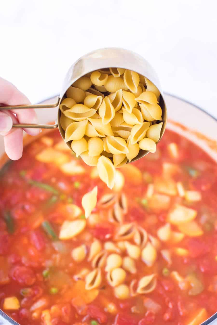 cup of pasta shells being poured into pot of minestrone soup