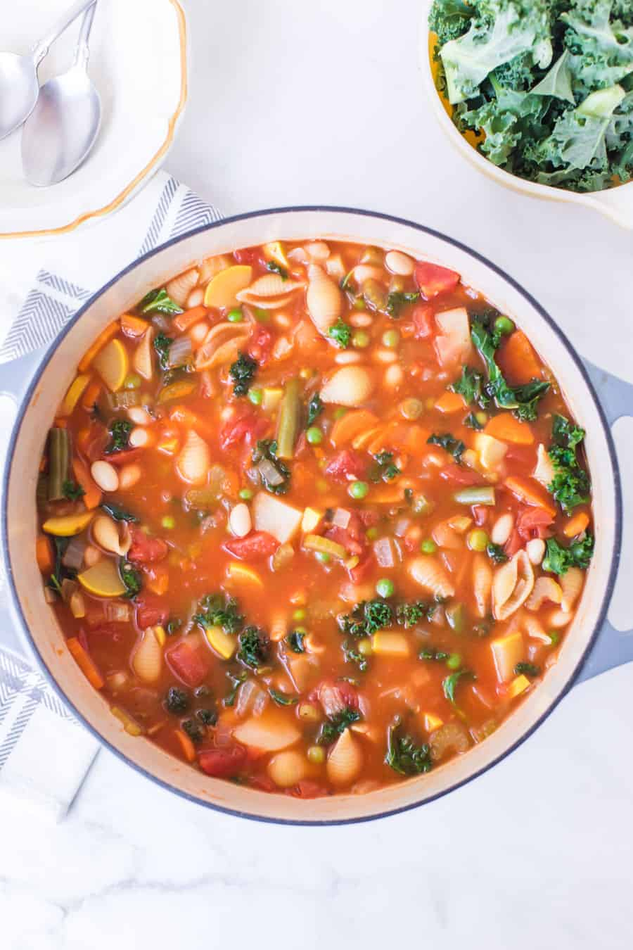 bowl of minestrone soup with cup of kale next to spoons