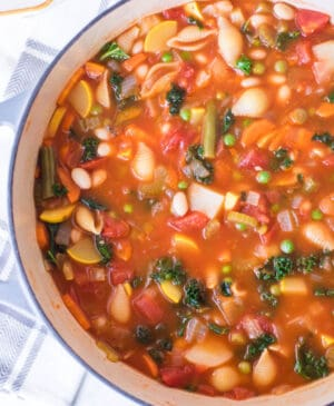 classic minestrone soup in round white bowl with blue rim