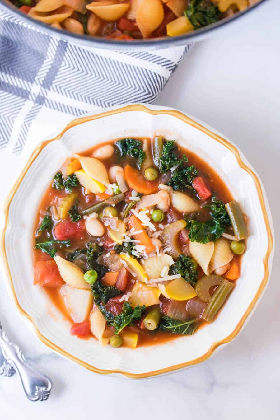 bowl of classic minestrone soup with spoons on blue checkered towel