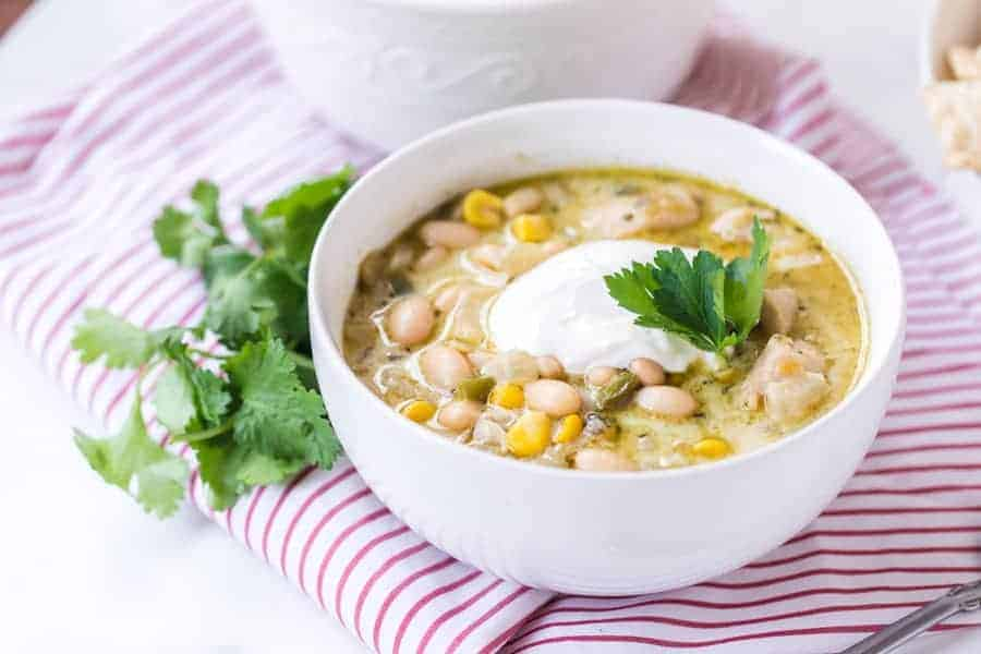 round white bowl of white bean chicken chili topped with sour cream and garnish on red and white striped towel