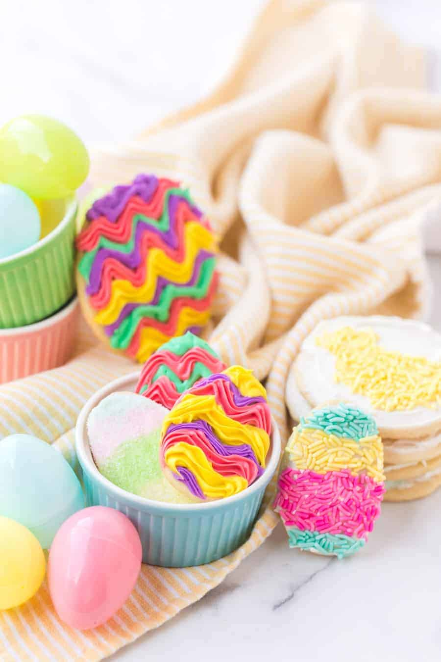 long image of iced sugar cookies and cookies with sprinkles in ramekins with plastic easter eggs on yellow and white striped towel