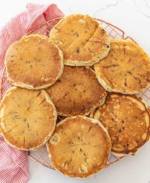 fluffy chocolate chip pancakes on cooling rack with red and white striped towel