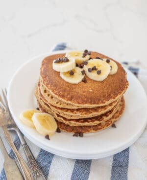 stack of banana pancakes on round white plate with banana slices on top of blue striped towel