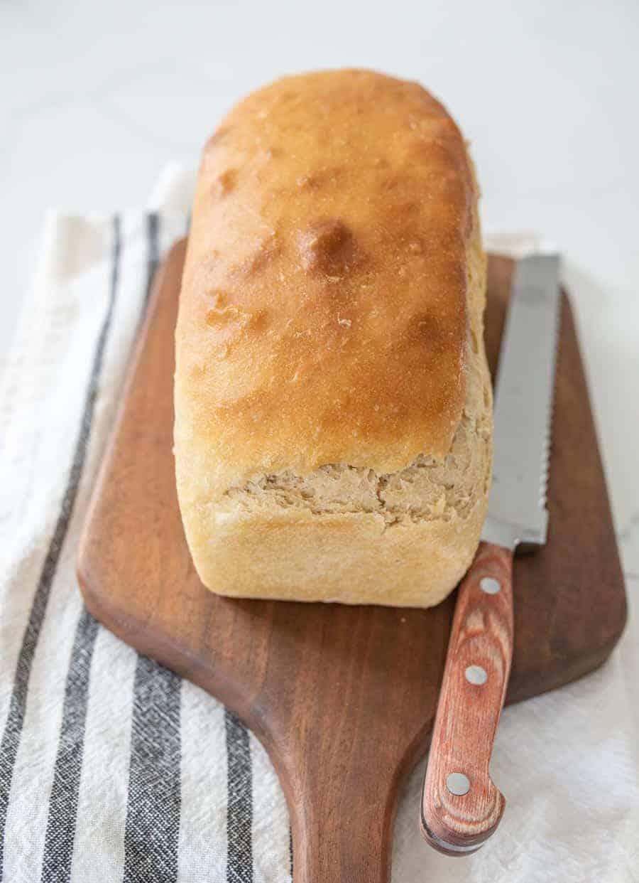 soft sandwich sourdough bread loaf uncut on wooden cutting board with knife