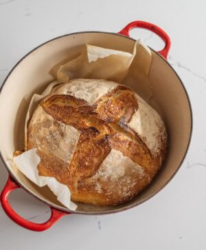 sourdough bread in dutch oven with red handles