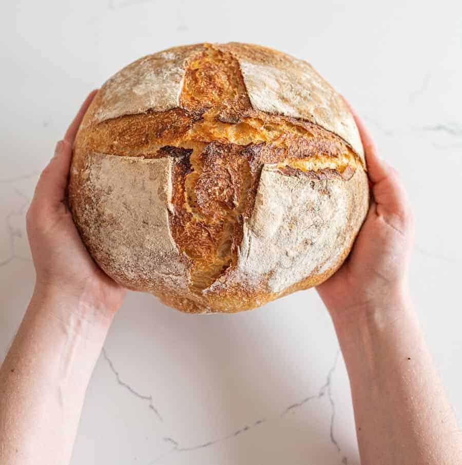 woman holding sourdough bread loaf