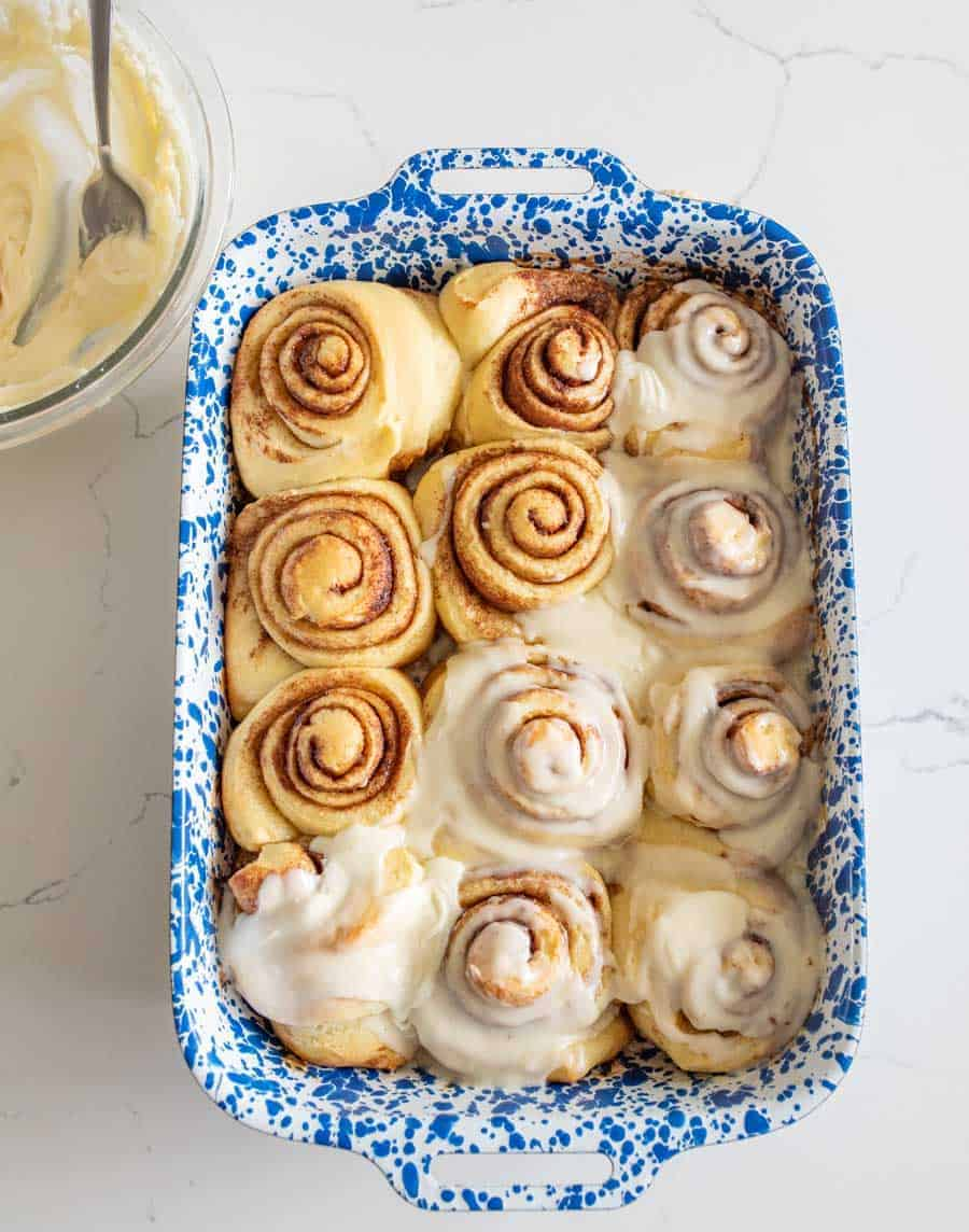 baked sourdough cinnamon rolls in blue and white pan half with buttercream frosting