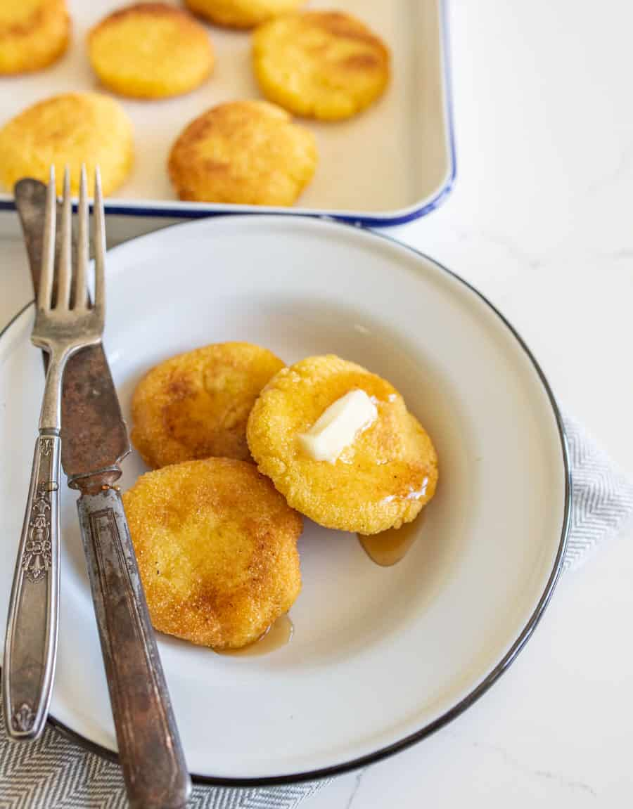 hot water cornbread with butter on white plate with knife and fork